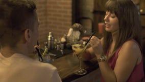 Pares en el hombre y la mujer del amor que beben el cóctel alcohólico que se sienta en el contador de la barra mientras que fecha almacen de metraje de vídeo