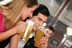Pares en el ligue de consumición de la cerveza de la barra Imágenes de archivo libres de regalías
