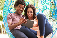 Pares en el oscilación al aire libre Seat del jardín usando la tableta de Digitaces Imágenes de archivo libres de regalías