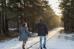 Pares en el parque del invierno que camina por el ferrocarril Familia al aire libre Amor Foto de archivo