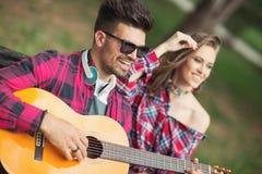 Pares en el parque que toca la guitarra y que canta canciones Fotografía de archivo