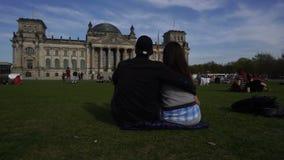 Pares en el prado del edificio de Reichstag, Berlín, Alemania almacen de video