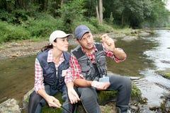 Pares en el río en un día de pesca Imagen de archivo libre de regalías