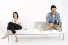 Pares en el sofá que ve la TV Fotos de archivo