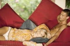 Pares en el sofá rojo el día de fiesta Fotografía de archivo libre de regalías
