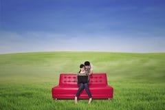 Pares en el sofá rojo usando el ordenador portátil al aire libre Foto de archivo
