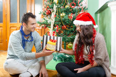 Pares en el sombrero de Papá Noel con el regalo de la Navidad y del Año Nuevo Foto de archivo libre de regalías