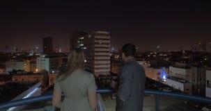 Pares en el tejado que mira la noche Tel Aviv y que tiene bebidas, Israel metrajes