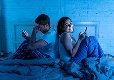 Pares en el teléfono móvil tarde en la noche en el apego social de la red y problemas nacionales de la relación foto de archivo libre de regalías