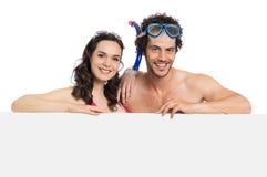 Pares en el traje de baño que lleva a cabo la muestra foto de archivo libre de regalías