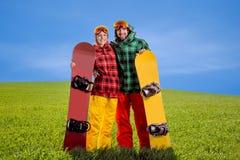 Pares en el traje de esquí que se divierte con las snowboard en la hierba en GR Fotos de archivo