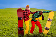 Pares en el traje de esquí que se divierte con las snowboard en la hierba en GR Foto de archivo