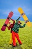 Pares en el traje de esquí que se divierte con las snowboard en la hierba en GR Foto de archivo libre de regalías
