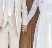Pares en el vestido de boda que lleva a cabo las manos Fotografía de archivo libre de regalías