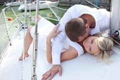 Pares en el yate en amor honeymoon Un hombre que besa a una mujer en el cuello mientras que miente en la cubierta foto de archivo libre de regalías