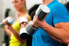 Pares en gimnasia que ejercita con pesas de gimnasia Fotos de archivo libres de regalías