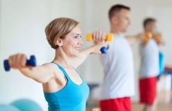 Pares en gimnasia que ejercita con pesas de gimnasia Imagenes de archivo