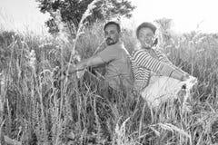 Pares en hierba verde grande de nuevo a la parte posterior Hombre y mujer que se sientan en el campo en día de verano pares de am fotos de archivo