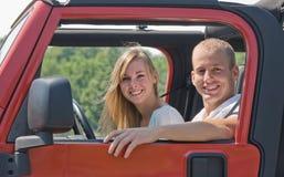 Pares en jeep rojo Foto de archivo