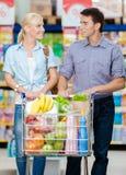 Pares en la alameda de compras con el carro lleno de comida Imágenes de archivo libres de regalías