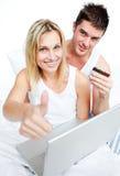 Pares en la cama que compra en línea con el pulgar para arriba Imagen de archivo libre de regalías