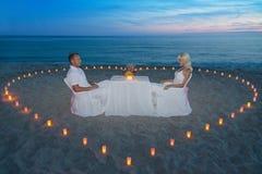 Pares en la cena romántica de la playa con el corazón de las velas Imágenes de archivo libres de regalías