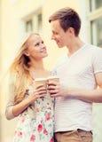 Pares en la ciudad con las tazas de café para llevar Fotografía de archivo libre de regalías