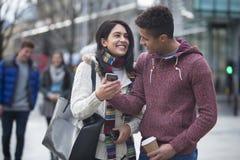 Pares en la ciudad que mira un smartphone Imagenes de archivo