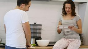 Pares en la cocina casera El hombre prepara la ensalada y a la mujer que usa la tableta electrónica almacen de metraje de vídeo