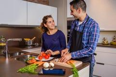 Pares en la cocina casera prepairing la comida sana Foto de archivo libre de regalías