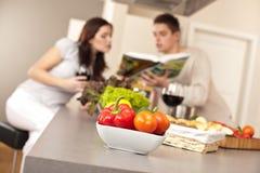 Pares en la cocina que elige receta del libro de cocina Imágenes de archivo libres de regalías