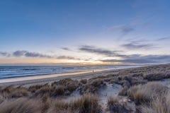 Pares en la distancia que camina a lo largo de la playa en la puesta del sol fotografía de archivo libre de regalías
