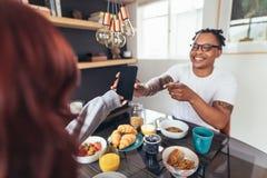 Pares en la mesa de desayuno con el teléfono foto de archivo libre de regalías