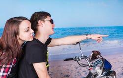Pares en la moto en la playa que mira a la derecha Fotografía de archivo