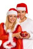 Pares en la Navidad con los sombreros de Papá Noel Imagenes de archivo