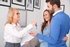 Pares en la oficina de ventas de las propiedades inmobiliarias con la nueva compra del apartamento del agente fotografía de archivo libre de regalías