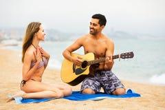 Pares en la playa con la guitarra Foto de archivo