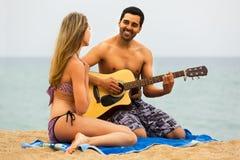 Pares en la playa con la guitarra Fotos de archivo libres de regalías