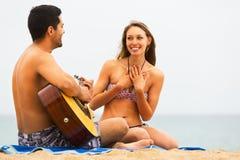Pares en la playa con la guitarra Fotografía de archivo