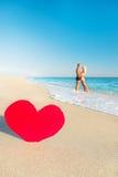 Pares en la playa del mar y el corazón rojo grande Foto de archivo