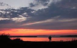 Pares en la playa en fondo de la puesta del sol Foto de archivo libre de regalías