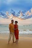Pares en la playa en la puesta del sol Foto de archivo
