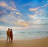Pares en la playa en la puesta del sol Imagenes de archivo