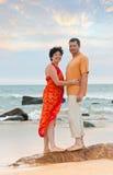 Pares en la playa en la puesta del sol Foto de archivo libre de regalías