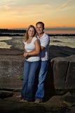 Pares en la playa en la puesta del sol Fotografía de archivo libre de regalías