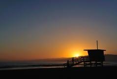 Pares en la playa en la puesta del sol imagen de archivo