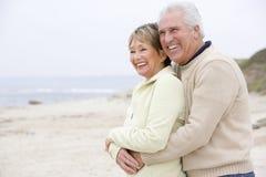 Pares en la playa que abraza y que sonríe Imágenes de archivo libres de regalías