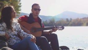 Pares en la playa que juega la canción del canto de la guitarra en un día de verano al lado del río de la montaña Imágenes de archivo libres de regalías