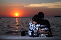 Pares en la playa que mira puesta del sol Fotografía de archivo