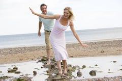 Pares en la playa que recorre en piedras y la sonrisa Imágenes de archivo libres de regalías